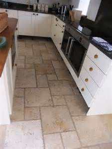 Stone tiles on a kitchen floor before and after cleaning and sealing