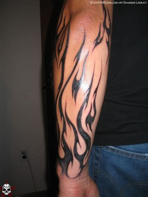 tribal black ink fire and flame tattoo on man sleeve