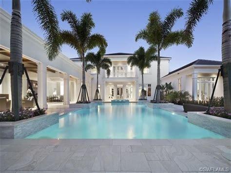 cool blue pool travertine deck royal palm trees white house grey oaks  naples fl