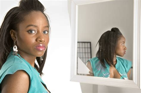 black woman looking in mirror why you might keep falling victim to unhealthy