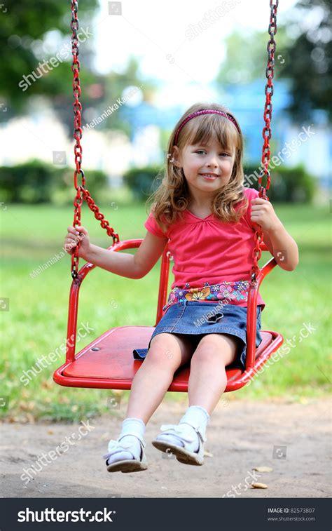 little girl on swing happy little girl smiling on swing stock photo 82573807