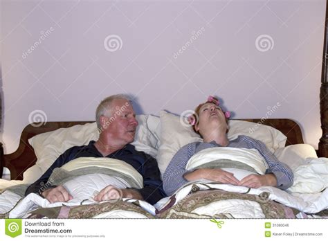 wife in bed man looking aghast at wife in bed royalty free stock image