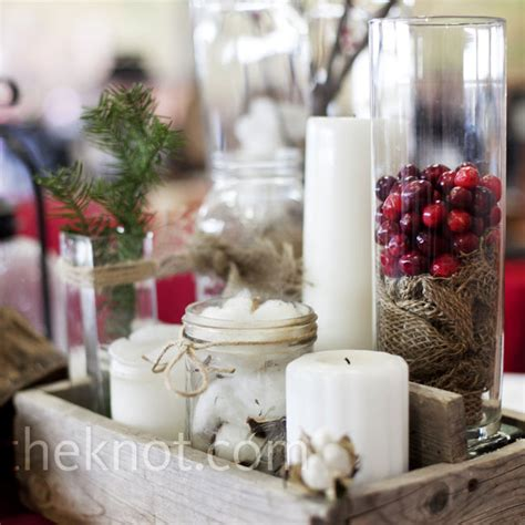 glass cylinders and jars filled with cranberries pine needles cotton and candles decorated