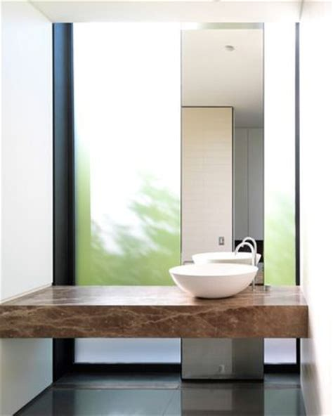 bathroom window height from floor wood slab vanity with full height mirror leaned on floor