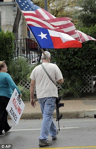 Gun rights activist phil newsome right carries a gun and flags as he