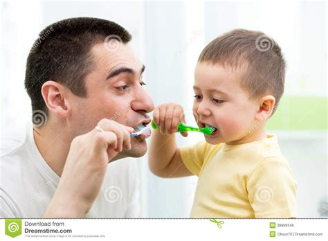dad in bathroom child boy and dad brushing teeth in bathroom stock photo
