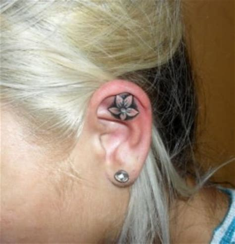 flower tattoo in ear with piercing flower tattoo on ear