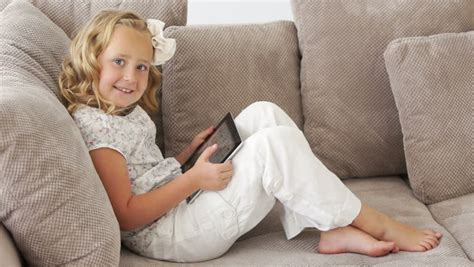little couch little girl lying on couch and playing on tablet pc stock
