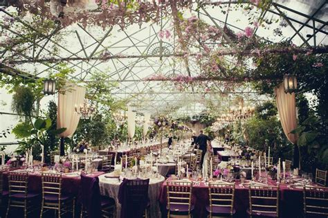 an indoor outdoor wedding reception in a greenhouse never