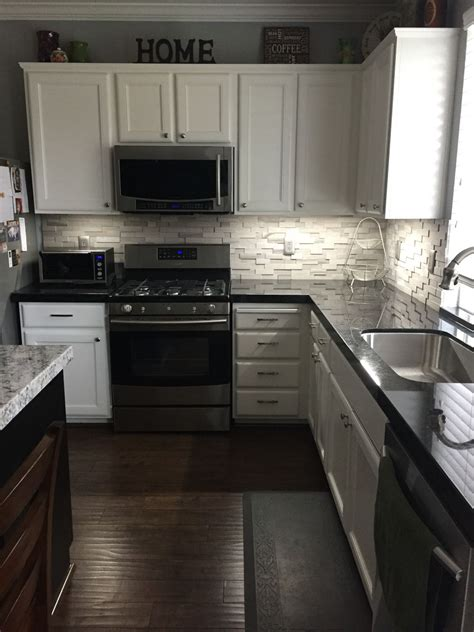 white cabinets with gray granite black granite with a gray backsplash for the home