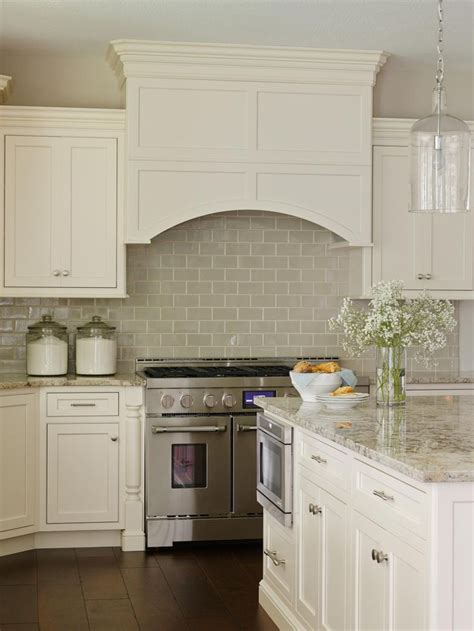 white tile kitchen backsplash off white cabinetry paired with a glossy neutral tile