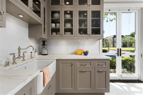 cabinet paint color is river reflections from benjamin moore beautiful warmer gray chelsea gray glass front kitchen cabinets with carrera marble