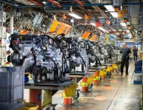 workers on engine production line in car factory the