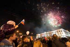 Vive la ruski a young boy waves a russian flag as people look at fire
