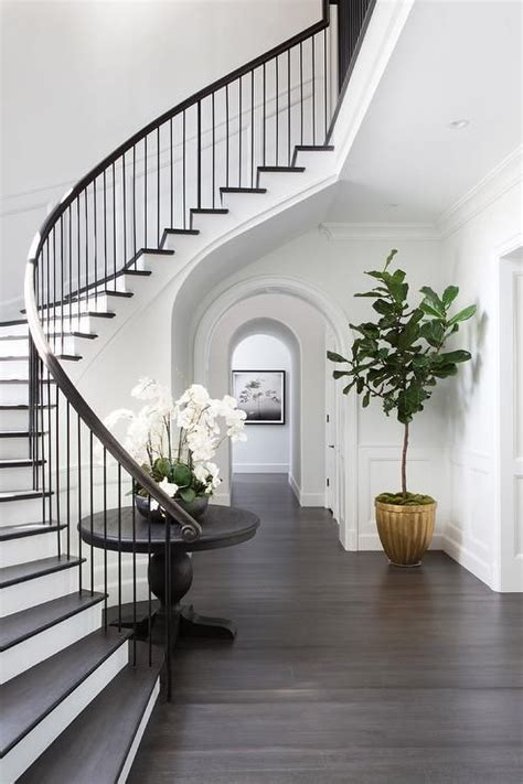 staircase design with dinning table chic classic foyer features a curved staircase wall filled with a black table and orchids