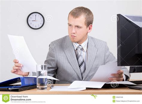 Online Paper Work From Home - worried accountant doing paperwork in office royalty free