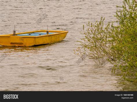small yellow boat small wooden yellow boat drifting image photo bigstock