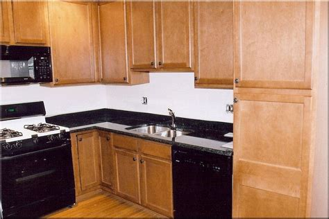 kitchen backsplash with oak cabinets and black appliances light colored oak cabinets with granite countertop