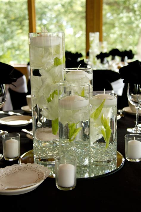Cylinder Vases With Floating Candles And Flowers varying heights of cylinder vases with floating flowers