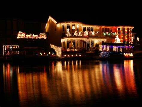 lakeside home and boat decked out in christmas lights