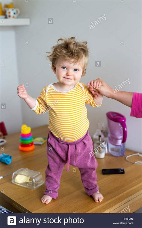 baby standing table one year baby standing up on table stock photo