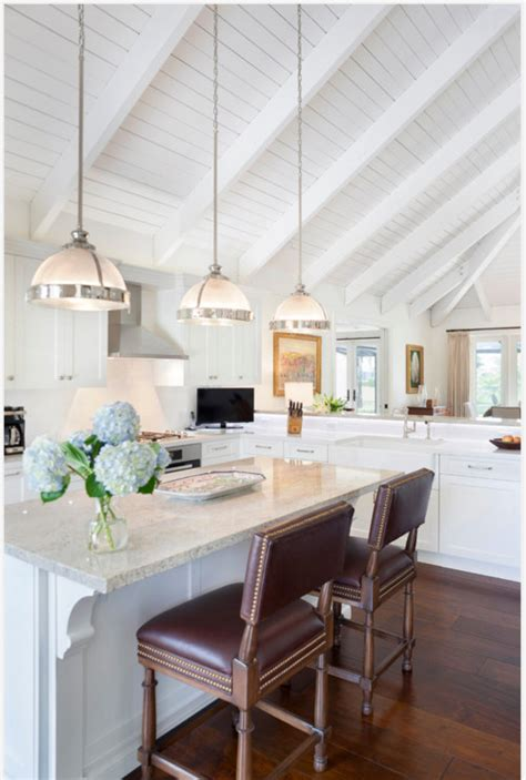 Kitchen Island Lighting For Vaulted Ceiling Three White Half Pendant Lights Hang From A Vaulted Ceiling A Marble Topped