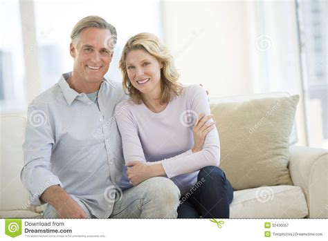 couple on sofa happy couple sitting on sofa in living room royalty free
