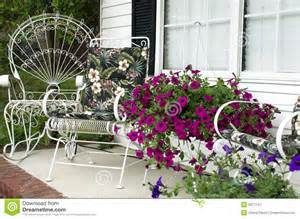 Home front porch with pots of petunias white metal outdoor furniture