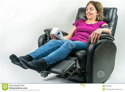 sitting in recliner while pregnant pretty middle age woman sitting in black leather recliner
