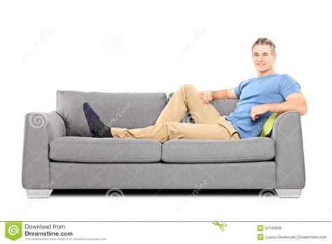 sitting in sofa relaxed young man sitting on a comfortable sofa stock