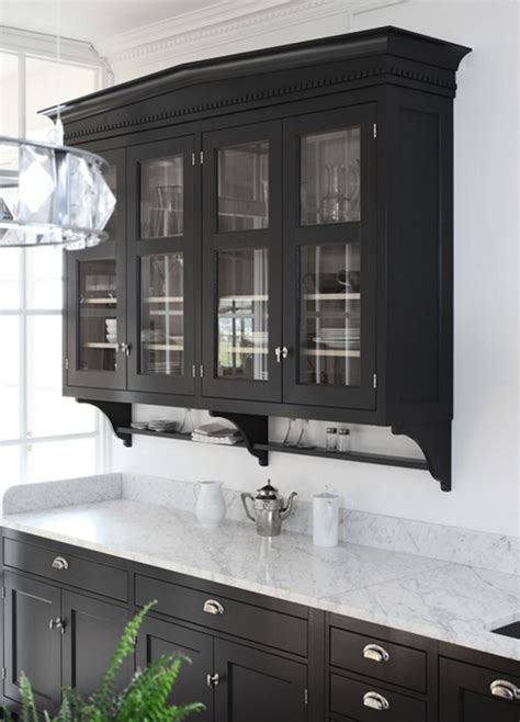 With glass front upper cabinets and black lower cabinets with white