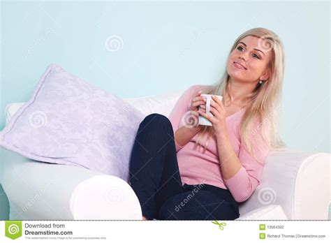 woman in an armchair woman sat in an armchair drinking tea stock photography