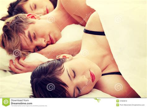 two girls in bed handsome man lying in bed with two girls royalty free