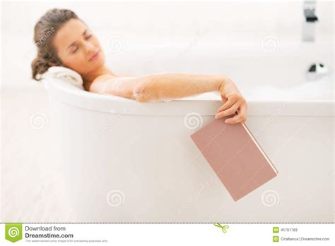 bathtub reading woman fall asleep while reading book in bathtub stock