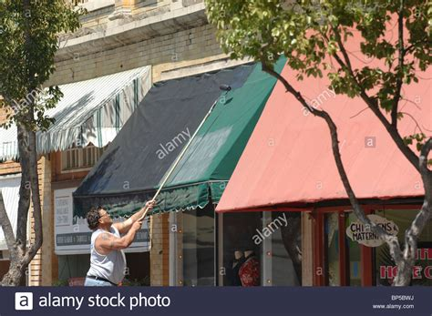 a on a ladder painting a green awning the