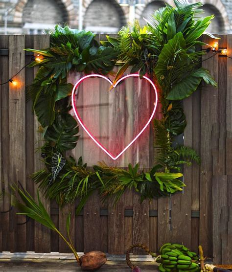Tropical backdrop with green leaves and neon heart by
