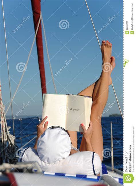 women on boats young woman reading and sunbathing on sail boat stock
