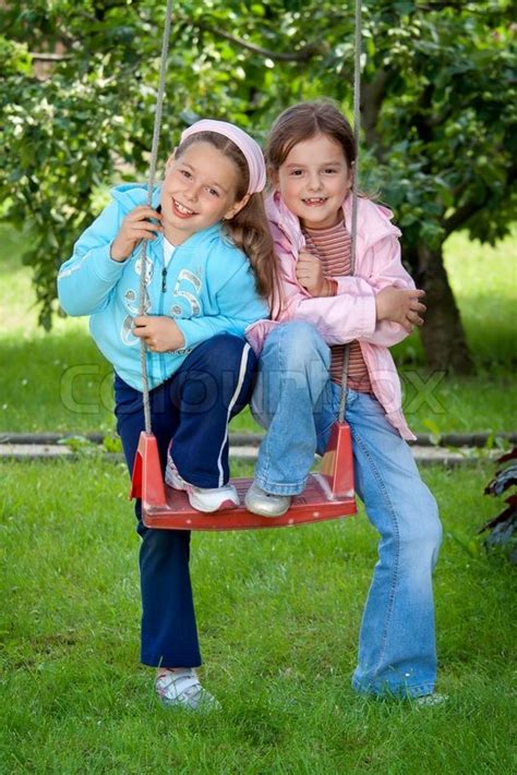 swing girl recess two young girls on the garden swing stock photo colourbox