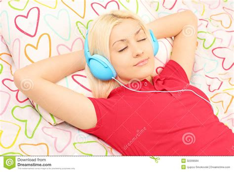 free music beds young female lying on a bed and listening music stock images image 32209584