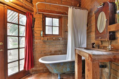 small rustic bathroom with weathered bathtub and brick backdrop decoist