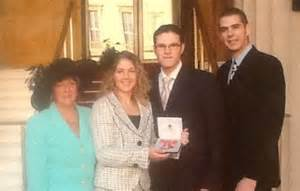 Cassie jackman holding her mbe alongside her mother patricia husband