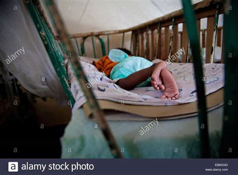 wearing diapers to bed baby in an orphanage sleeping in a bed with lattice bars