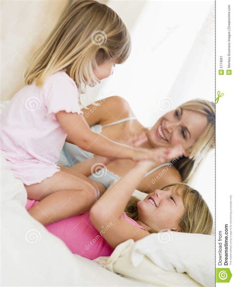 two girls in bed woman and two young girls in bed playing stock image