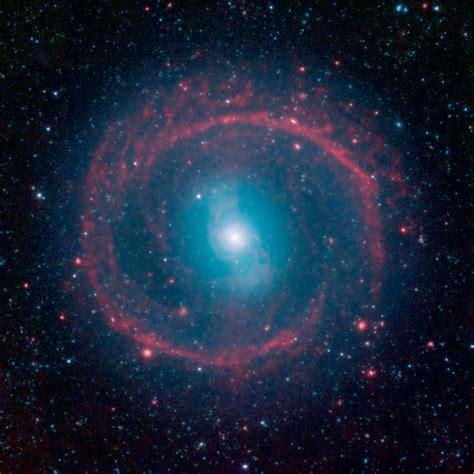 galaxy cosmic cosmic pinwheel surrounds distant galaxy in stunning nasa