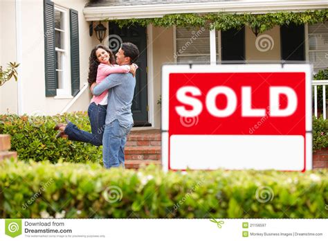 First Home Housewarming Gift hispanic couple outside home with sold sign royalty free