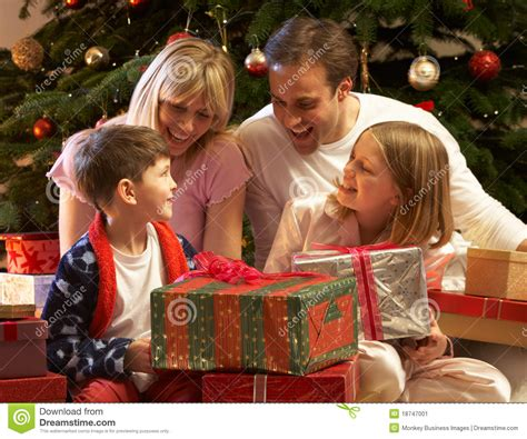 family christmas tree jarrettsville family opening present in front of tree stock image image 18747001