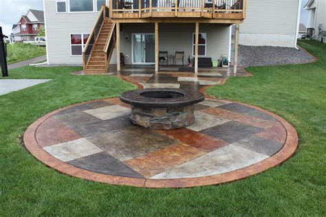 stained concrete patio with a wrapped pit
