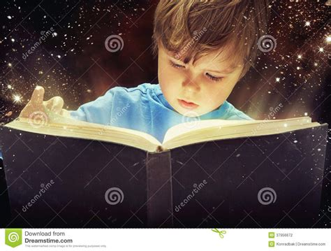 Yong Magic amazed boy with magic book stock photography image
