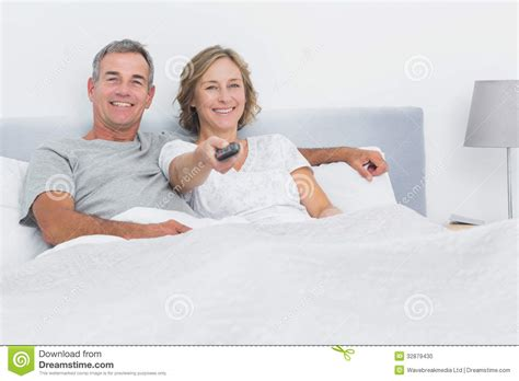 watching tv in bed relaxed couple watching tv in bed looking at camera stock
