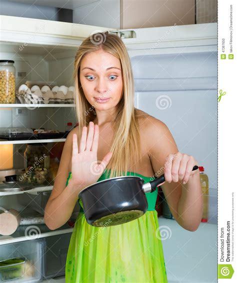 holding foul food near fridge stock photo image